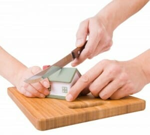 two hands cutting a house in two; needing a property division lawyer